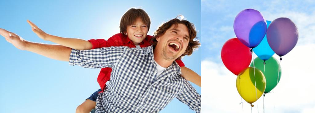 Ein Kind liegt auf dem Rücken eines Mannes, beide strecken die Arme weit aus und lachen