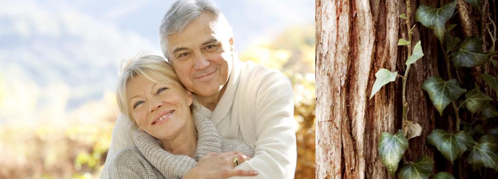 Ein älters Ehepaar hält umarmt sich lächelnd